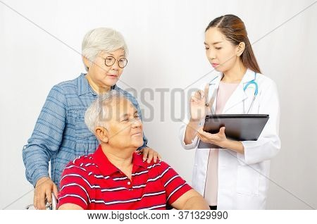 Asian Woman Doctor Talking To Senior Couple In Wheelchair At Hospital. Beautiful Asian Doctor Taking