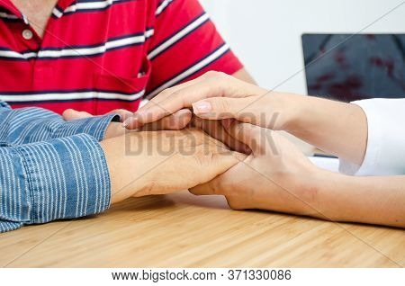 Female Doctor Soothes A Female Patient In Hospital Consulting Room While Holding The Patients Hands.