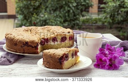 Cherry Homemade Cake And A Cup Of Tea In Nature