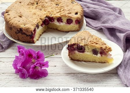 Homemade Cherry Pie And Slice On Plate With Lilac Napkin And Flower