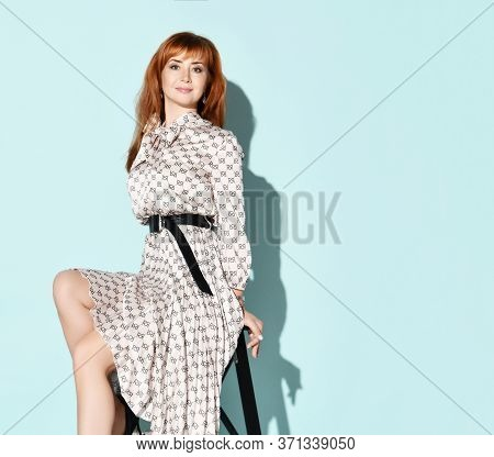 Young Beautiful Smiling Red-haired Woman In Elegant Light Dress With Bow And Black High Heel Shoes S