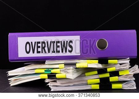 Text Overviews Is Written On A Folder Lying On A Stack Of Papers On A Table. Business Concept