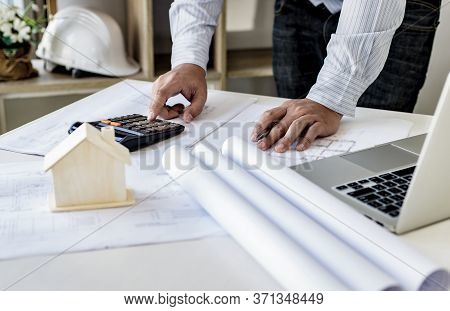 The engineer designed the house structure in the blueprint and working in the architect's room, Ther