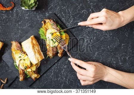 Female Hands Holds Sandwich With Eggs Benedict, Bacon And Salad On Black Stone Background. Top View