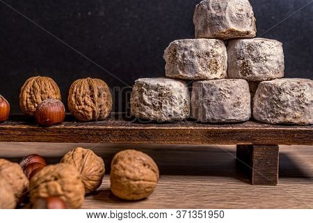 French Cheese Crottin De Chavignol In The Dark Background. Composition With Hazelnuts And Walnuts. H