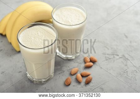 Banana Smoothie With Almond Milk In Glass On Grey Background