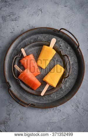 Papaya And Mango Popsicle On Round Metal Tray On Grey Background, Top View