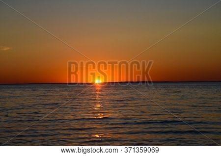 Bright Sunset Over The Lake. Orange Sun. Sunny Path In Calm Water. Yellow Sunset. Dark Water. The Su