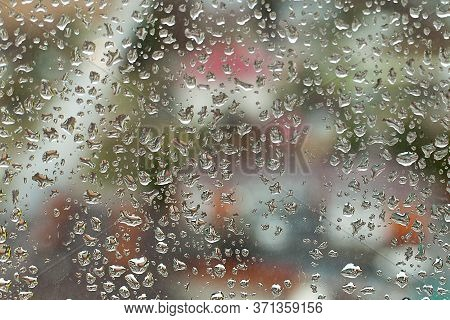 Rain Water Droplets With Houses In Background In City With Dark Clouds. Rain Water Droplets On Glass