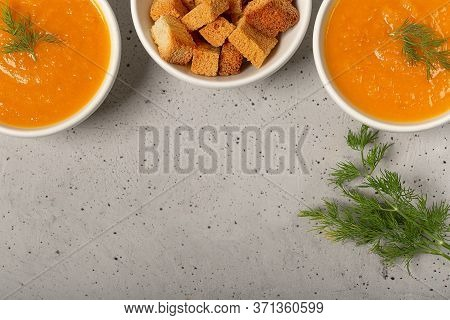 Pumpkin And Carrot Soup With Fresh Dill On Table