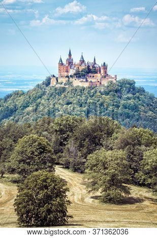 Castle Hohenzollern On Top Of Wooded Mountain, Baden-wurttemberg, Germany. Famous Burg Hohenzollern