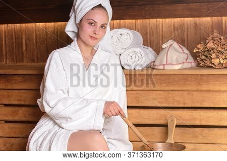 Beautiful Young Woman In A White Towel Is Relaxing In A Sauna. Sauna Made Of Wood. Concept: Relaxati