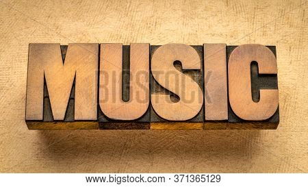 music  - word abstract in vintage wood letterpress printing blocks against textured paper