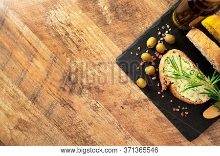 Sliced Bread And Rustic Handmade Herbs Butter On The Table.