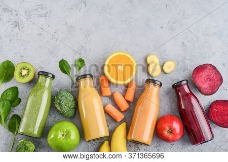 Green, Yellow, Orange And Red Smoothie In Glass Bottles With Fruits And Vegetables On Grey Backgroun