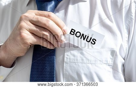 Bonus Word On Business Paper Card Held By A Man In Shirt And Tie. Man Putting A Card With Bonus Word