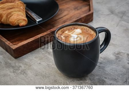 A Cup Of Coffee With Latte Art On Top And Butter  Croissant On Tray Closeup