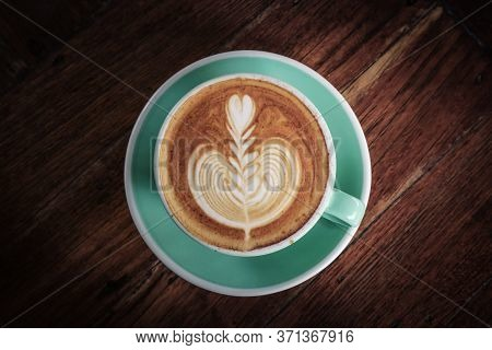 A Cup Of Coffee With Latte Art On Top On Dark Wooden Background, Top View