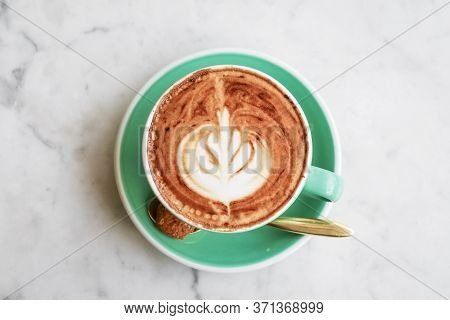 A Cup Of Coffee With Latte Art On Top On Light Background, Closeup Top View