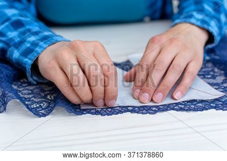 A Seamstress In A Blue Checked Shirt Is Working In Her Workshop. Close-up, On The Table, She Tries O