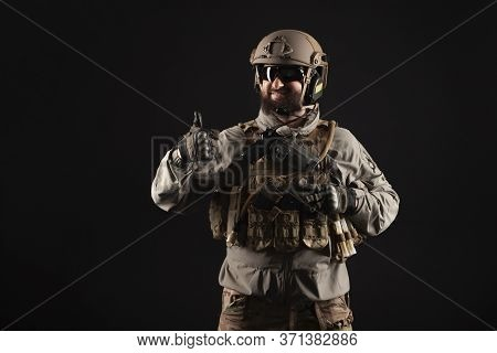 Usa Soldier In A Military Suit With A Rifle Smiles And Shows A Like Against A Dark Background, An Am