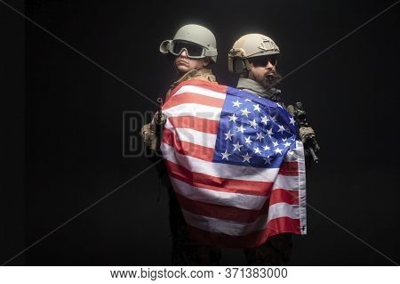 American Special Forces. Two Rangers In Uniform With Weapons Stand Together Against A Dark Backgroun