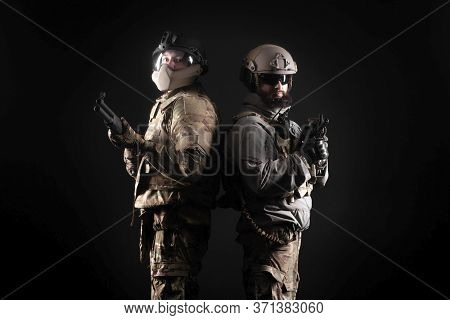 American Special Forces. Two Rangers In Uniform With Weapons Stand Together Against A Black Backgrou