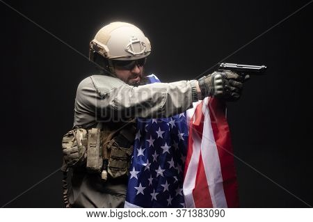 Army Of America. A Soldier In Military Equipment With A Gun Holds The Usa Flag On A Black Background