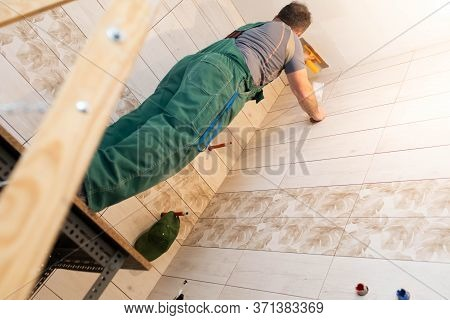 Applying Gypsum Finish On The Ceiling Of The Renovated Bathroom. Construction Worker In Middle Age.