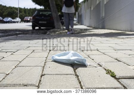 Used Lost Protective Medical Face Mask On The Ground. Disposable Face Mask Lying In The Street. Impr