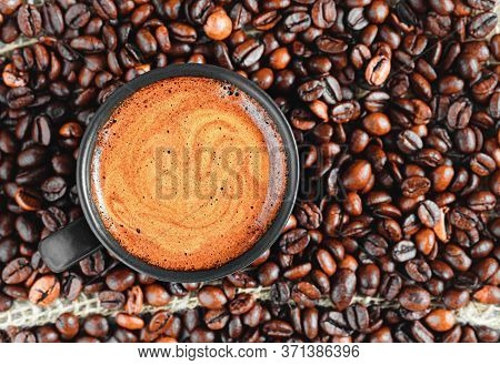 Espresso Cup With Froth Among Roasted Coffee Beans, Flat Lay, Close-up. Strong Aromatic Coffee