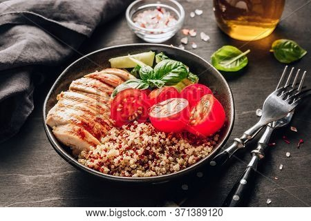 Healthy Salad Bowl With Quinoa, Tomatoes, Chicken, Cucumber And Basil On Black Wooden Background. Su