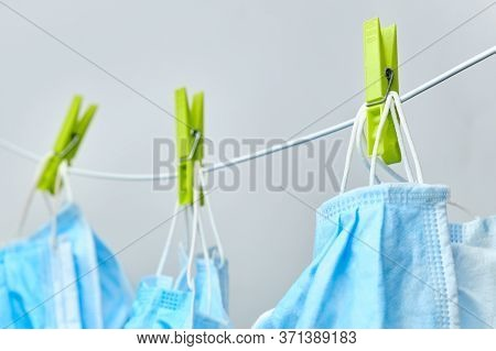 Drying Of Blue Protective Surgical Masks On Clothesline With Green Clothespins On A White Background