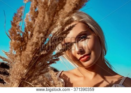 Portrait Of A Beautiful Girl, Blonde With Long Hair In A Field A Sunny Day At Sunset.