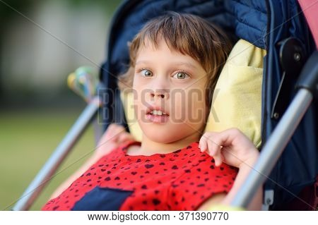 Portrait Of A Cute Little Disabled Girl In A Wheelchair. Child Cerebral Palsy. Disability. Inclusion