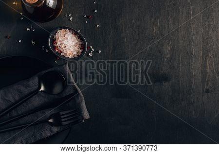 Black Table Setting: Plate, Napkin, Silverware, Olive Oil And Salt On Black Wooden Background. Top V