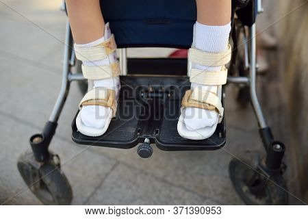 Disabled Girl Sitting In Wheelchair. On Her Legs Orthosis. Close Up Photo. Child Cerebral Palsy. Dis
