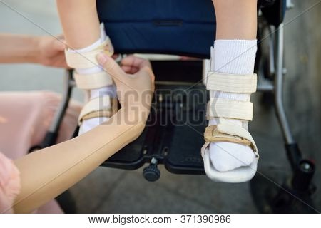 Mother Puts On Her Daughter Legs Orthosis. Disabled Girl Sitting On A Wheelchair. Child Cerebral Pal