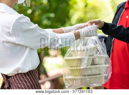 Close up waitress hand give food box to deliverly man to deliver it to customer make online order. Food deliverly service concept in new normal after coronavirus pandemic.