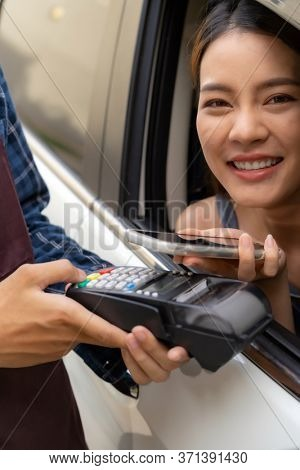Asian woman customer make mobile payment contactless technology to waiter in drive thru food service while pickup coffee and bakery. Drive through is more  popular after coronavirus covid-19 pandemic.