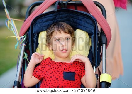 Portrait Of A Cute Little Disabled Girl In A Wheelchair. Child Cerebral Palsy. Inclusion. Disability