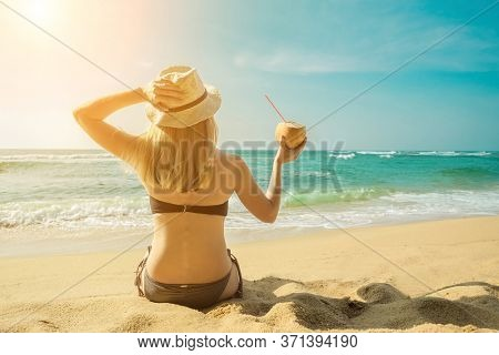 Happy Young Tourist  Smiling Caucasian Woman in hat with coconut in her hands on beach at sunny day. Beautiful Sunset light on coastline.
