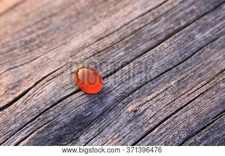 One Isolated Red Orange Chalcedony Agate Gemstone On Wooden Background Shining In The Sunlight. Chal