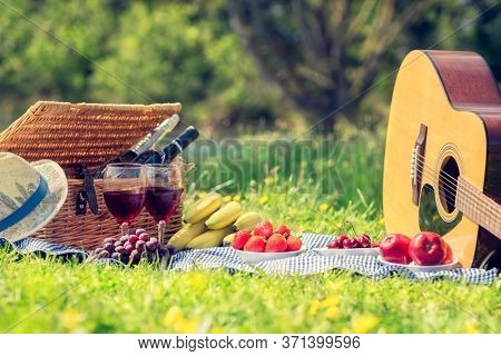 Picnic setting with red wine, glasses, bottle, picnic hamper basket, guitar and food ready for party