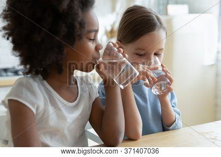 Two Multiracial Girls Sit In Kitchen Feels Thirsty Drink Water