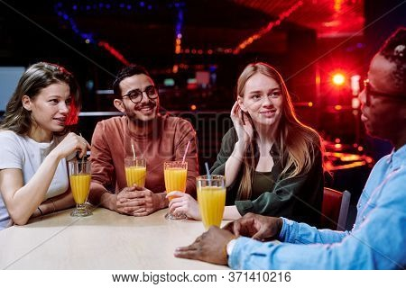 Two girls of Caucasian ethnicity and mixed-race guy listening to their African friend telling them about himself by glass of juice in bar