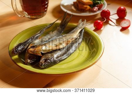 Salted Undivided Fish On A Plate And A Mug Of Beer On A Wooden Table