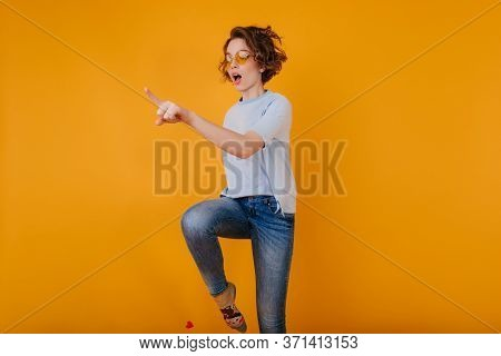 Beautiful White Woman In Trendy Denim Pants Jumping On Yellow Background. Joyful Female Model With W