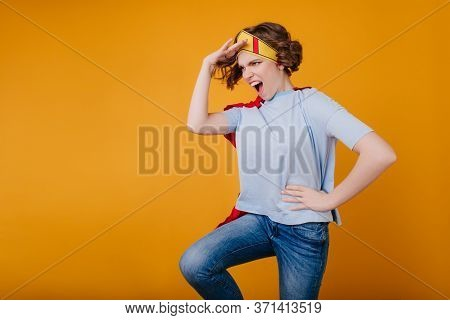 Funny Girl In Paper Yellow Crown Fooling Around On Photoshoot. Glad Young Woman In Jeans Preparing F