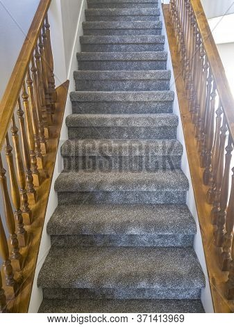 Indoor Staircase With Carpeted Treads And Brown Wooden Handrails And Balusters